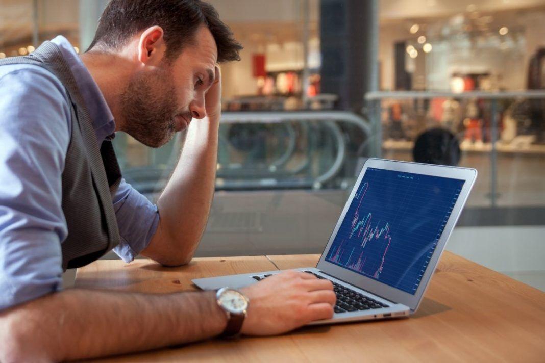 Zmartwiony trader przegląda wykresy giełdowe